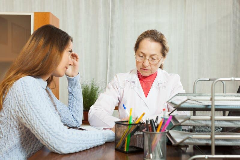 Docteur de femme et patient d'adolescent image libre de droits