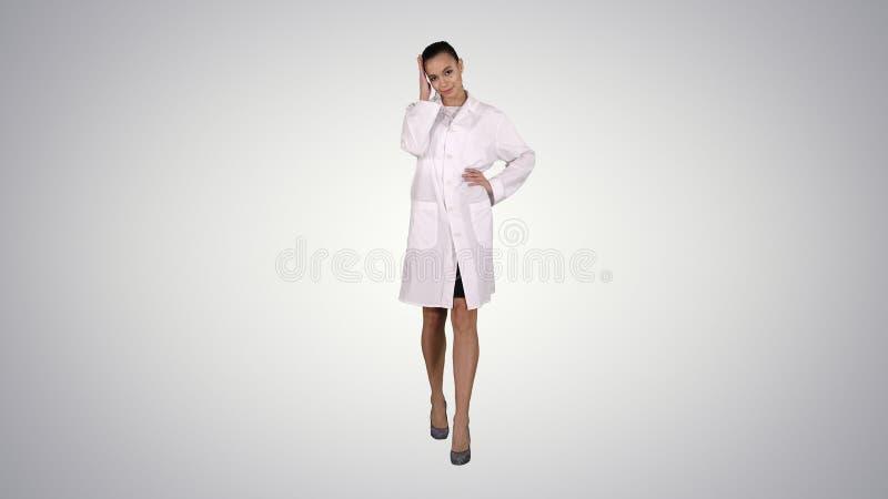 Docteur de femme marchant comme le mannequin sur le fond de gradient images libres de droits