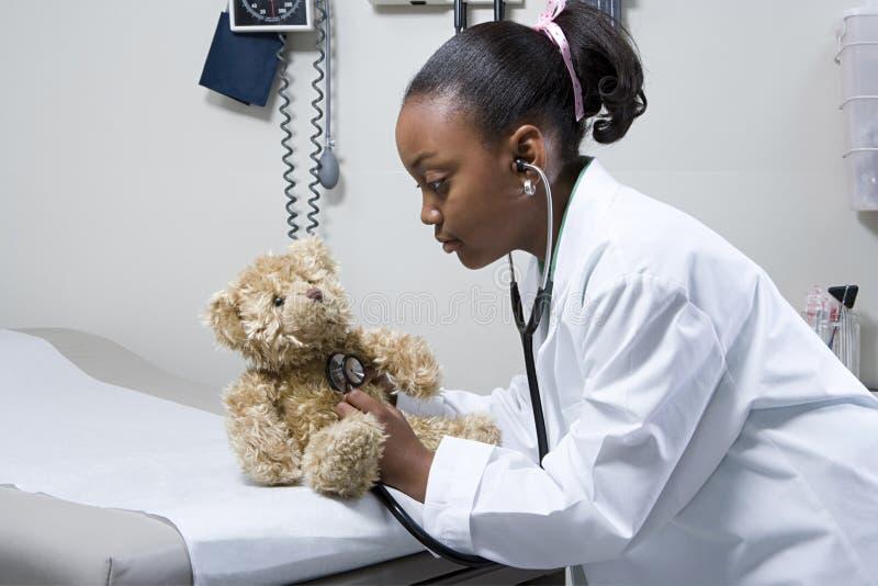 Docteur de fille à l'aide du stéthoscope sur l'ours de nounours photo libre de droits
