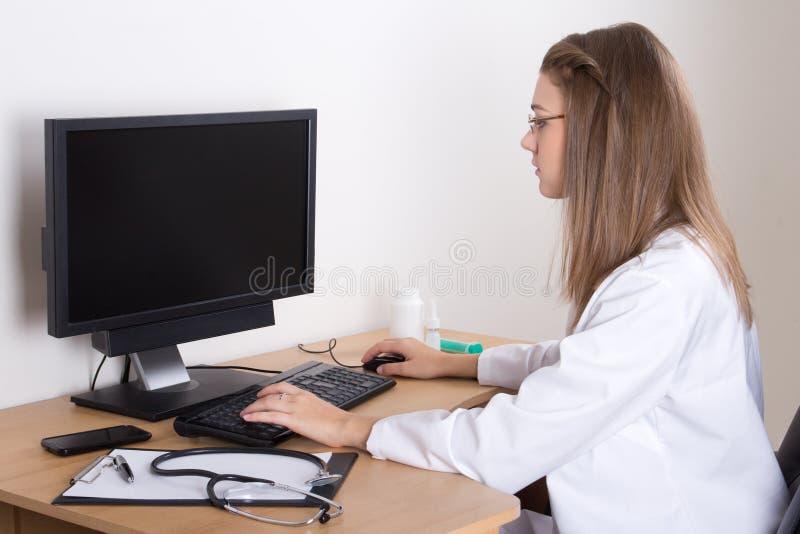 Docteur de jeune femme à l'aide de l'ordinateur avec l'écran vide photos stock