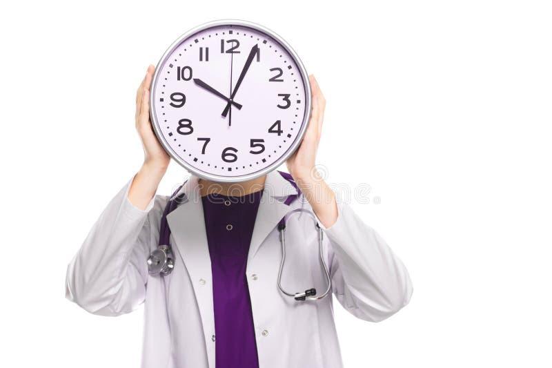 Docteur de jeune femme avec le stéthoscope dans le problème tenant l'horloge devant sa tête dans l'uniforme blanc sur le fond bla image libre de droits