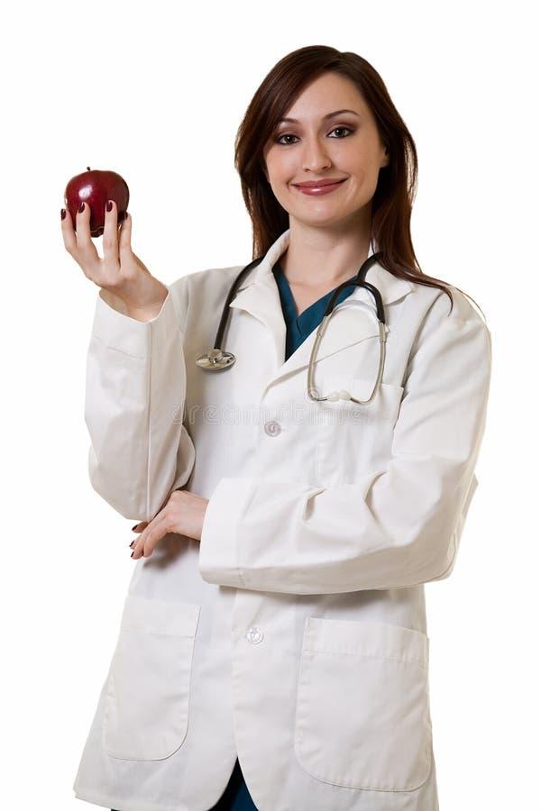 Docteur de Madame avec la pomme photo stock