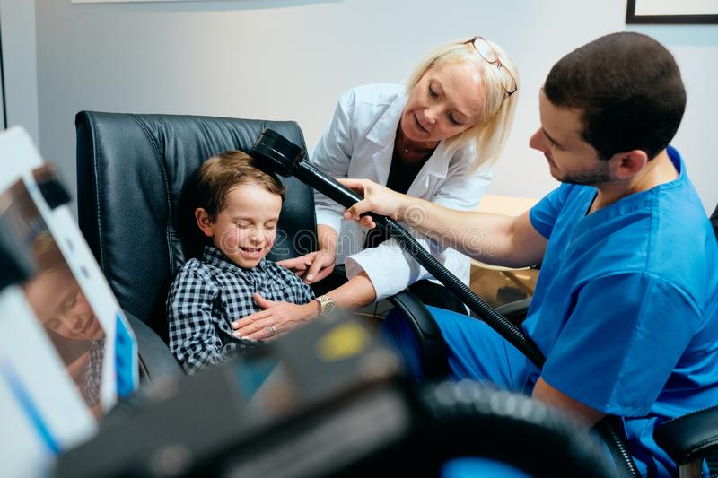 Docteur de pédiatre Doing Brain Treatment To Autistic Child dans la clinique photos stock