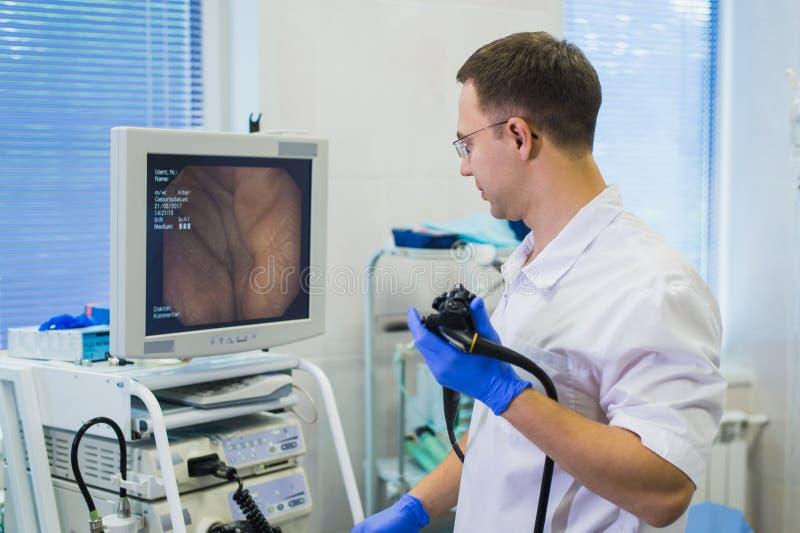 Docteur de Proctologist jugeant Ligador hemorroidal dans le bureau photographie stock