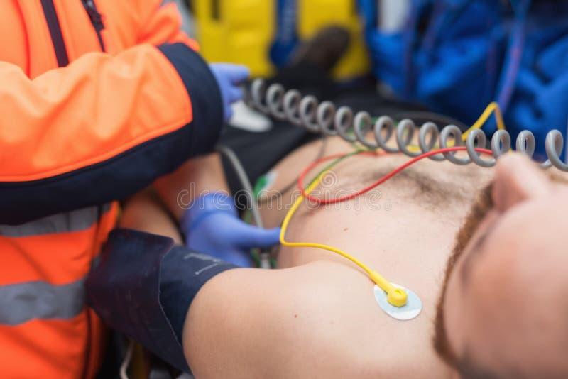 Docteur de secours vérifiant la tension artérielle d'un patient dans l'ambulance image libre de droits