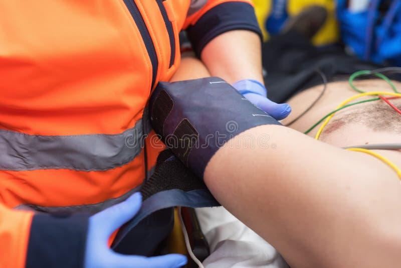Docteur de secours vérifiant la tension artérielle d'un patient dans l'ambulance images libres de droits