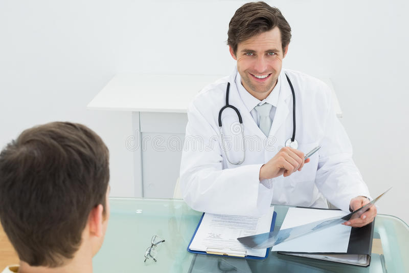 Docteur de sourire expliquant des rapports de rayon X au patient image libre de droits