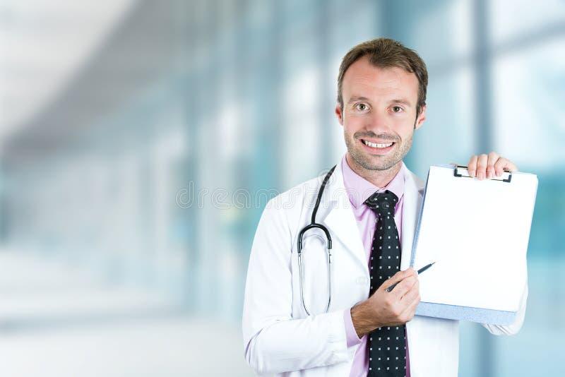 Docteur de sourire heureux avec le presse-papiers se tenant dans le couloir d'hôpital images libres de droits