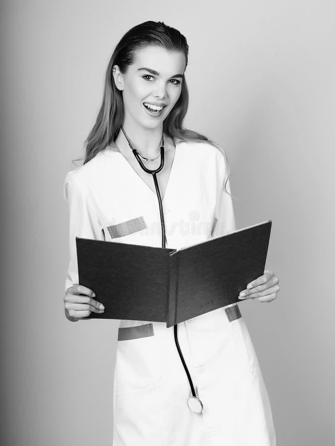 Docteur de sourire heureux tenant le journal médical rouge photo stock