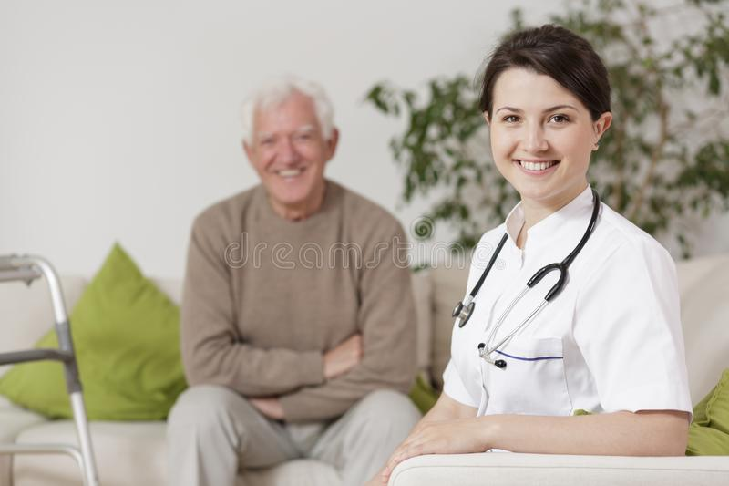 Docteur de sourire pendant la visite à la maison photographie stock