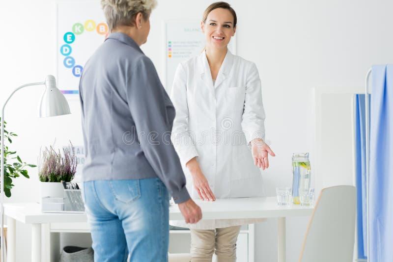 Docteur de sourire souhaitant la bienvenue au patient image libre de droits