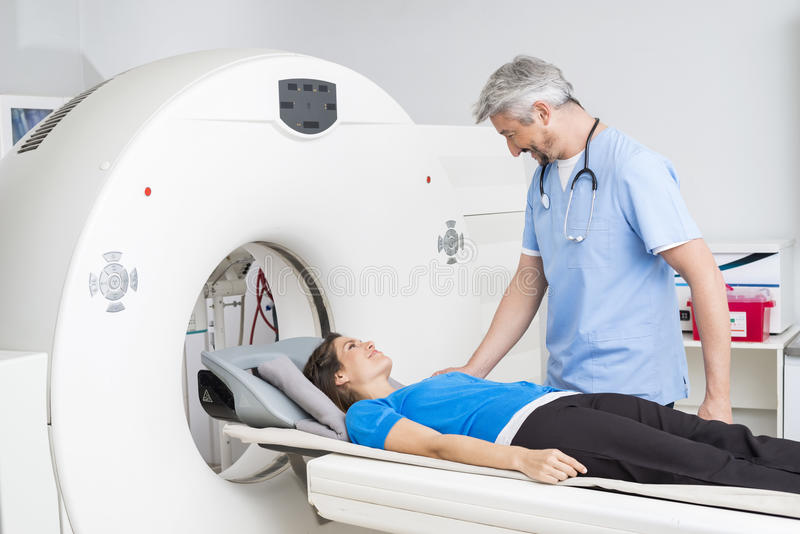 Docteur de sourire Talking To Patient se trouvant sur la machine de balayage de CT photo stock