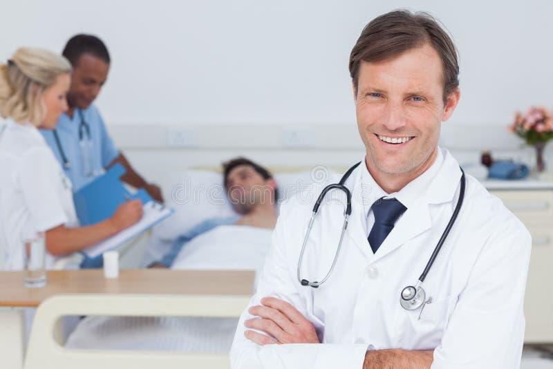 Docteur de sourire tenant et regardant l'appareil-photo photographie stock libre de droits
