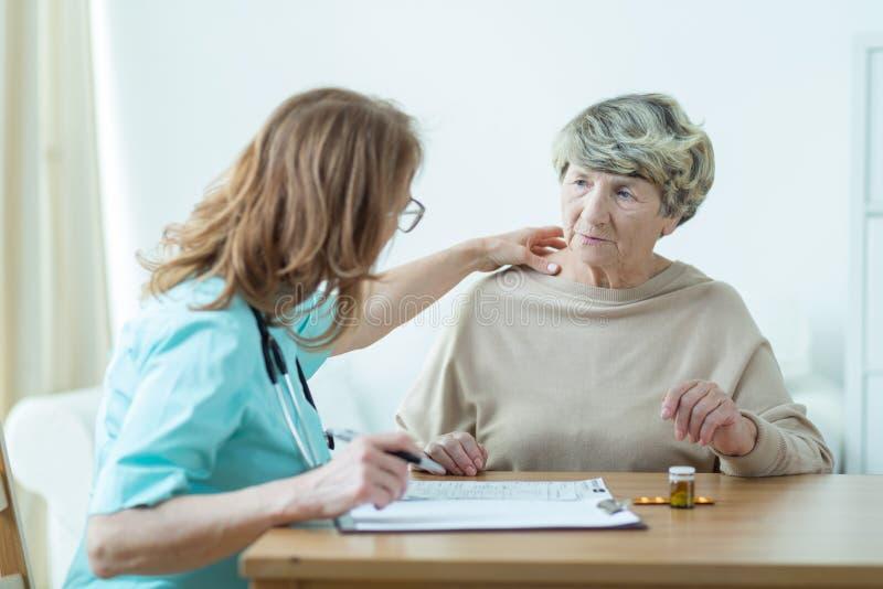 Docteur diagnostiquant une femme plus âgée image libre de droits