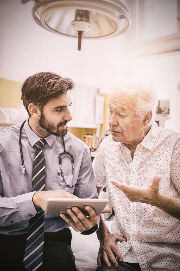 Docteur discutant avec le patient au-dessus du comprimé numérique images libres de droits