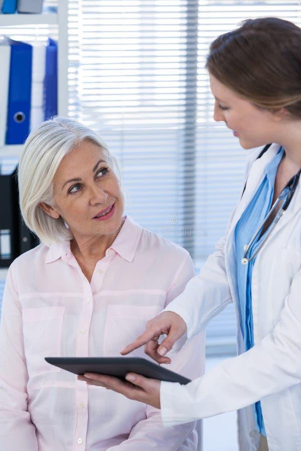 Docteur discutant avec le patient au-dessus du comprimé numérique image libre de droits
