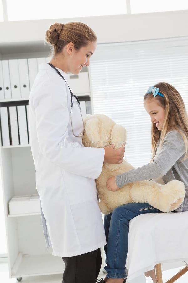 Docteur donnant à un patient un ours bourré photos libres de droits