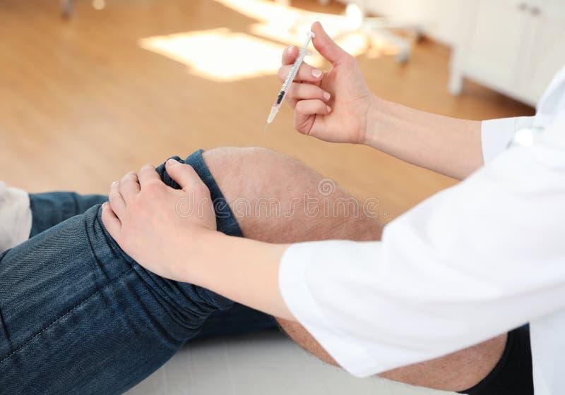 Docteur donnant l'injection patiente dans la clinique Traitement de problème de genou photo libre de droits