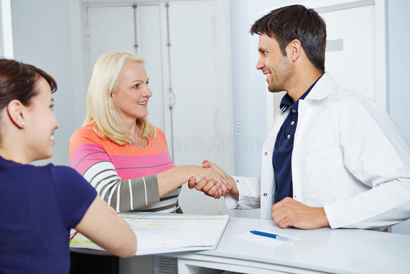 Docteur donnant la poignée de main patiente supérieure photo stock