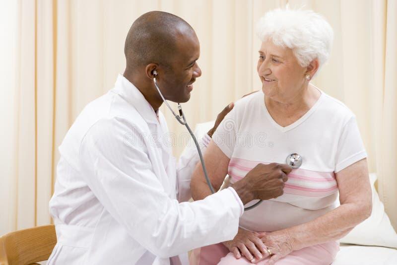 Docteur donnant le contrôle avec le stéthoscope au femme image libre de droits
