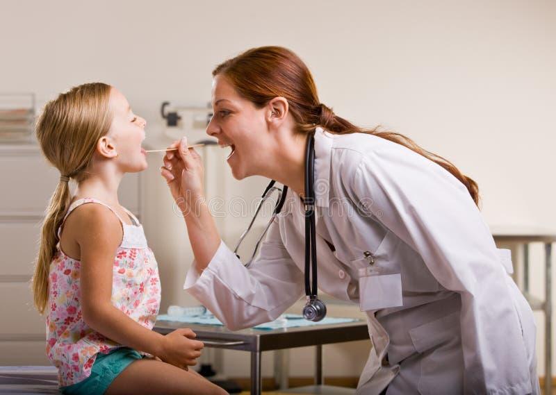 Docteur donnant le contrôle de fille dans le bureau de docteur photographie stock libre de droits