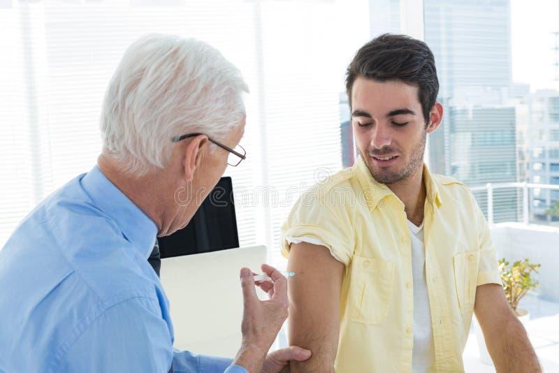 Docteur donnant une injection au patient images libres de droits