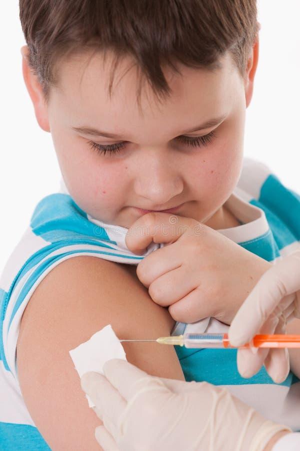 Docteur donnant une injection d'enfant dans le bras images libres de droits