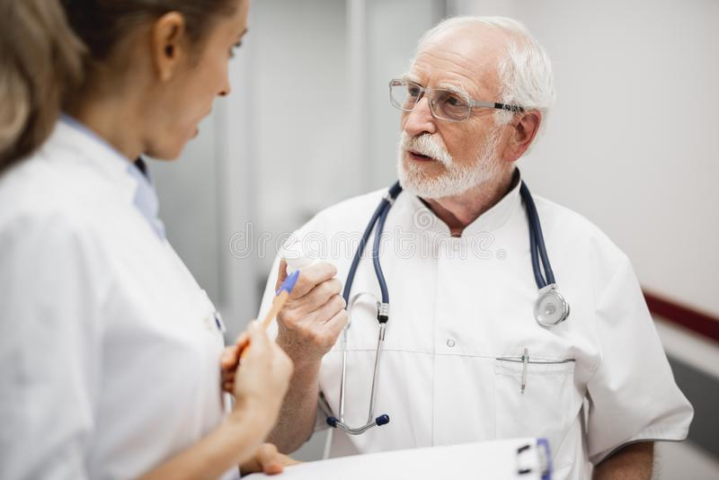 Docteur en verres parlant avec l'infirmière tout en tenant la bouteille avec des pilules photo stock