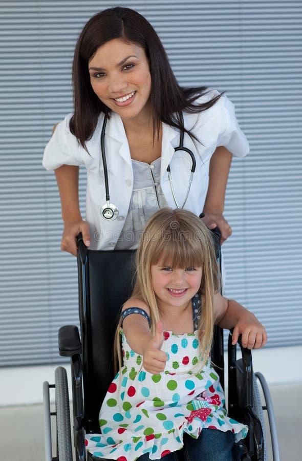 Docteur et fille de sourire sur un fauteuil roulant images stock