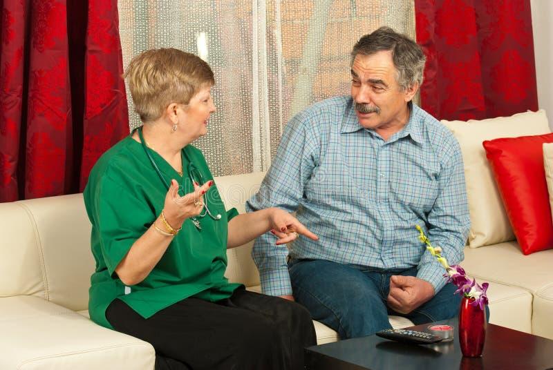 Docteur et homme aîné ayant la conversation photo stock