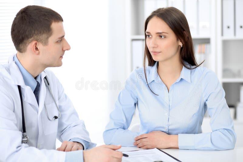 Docteur et patient s'asseyant au bureau Concept de médecine et de soins de santé image libre de droits