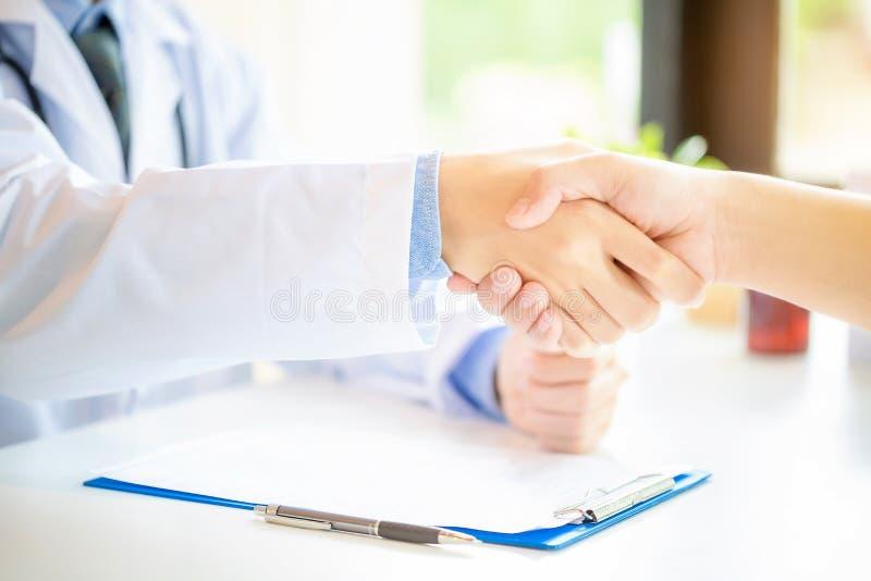 Docteur et patient se serrant la main dans le bureau images libres de droits