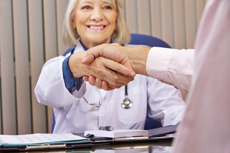 Docteur et poignée de main donnante patiente après consultation photos libres de droits