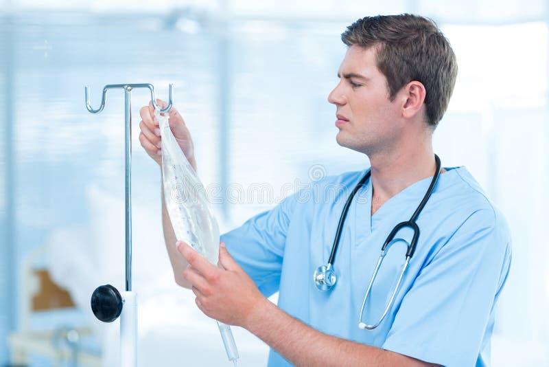 Docteur examinant l'égouttement intraveineux photographie stock libre de droits
