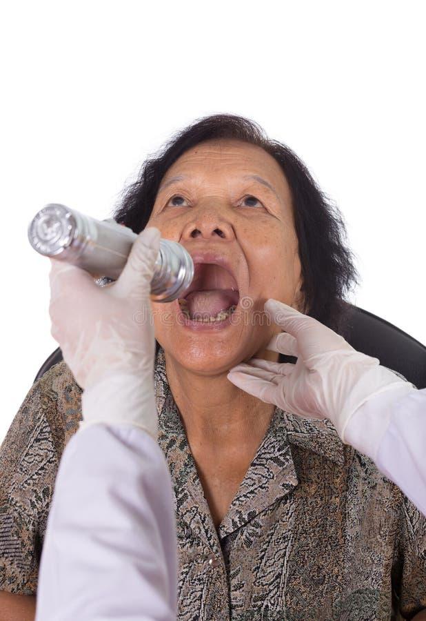 Docteur examinant la femme supérieure pour assurer l'angine photos stock
