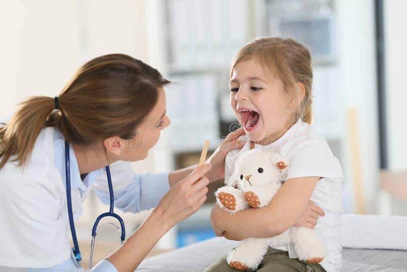 Docteur examinant la gorge de l'enfant photo libre de droits