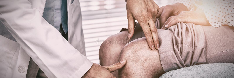 Docteur examinant le genou patient photos stock