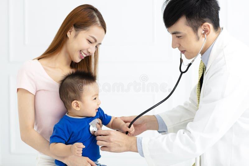 Docteur examinant le petit garçon par le stéthoscope images libres de droits