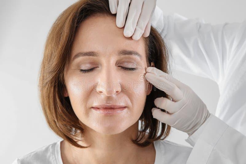 Docteur examinant le visage mûr de femme avant la chirurgie esthétique photographie stock libre de droits