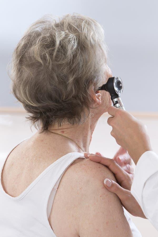 Docteur examinant les oreilles du patient plus âgé image stock