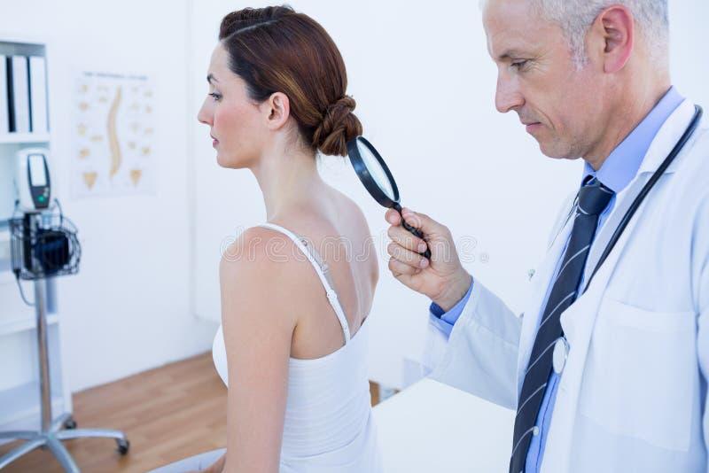 Download Docteur Examinant Son Dos De Patient Avec La Loupe Photo stock - Image du clinique, caucasien: 56484214