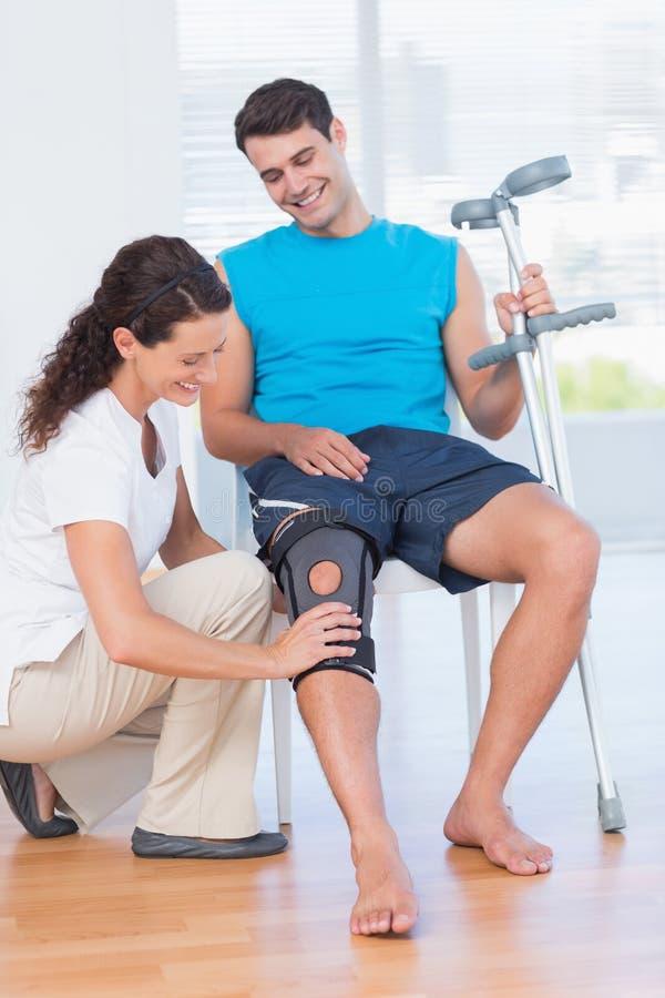 Docteur examinant son genou patient images stock