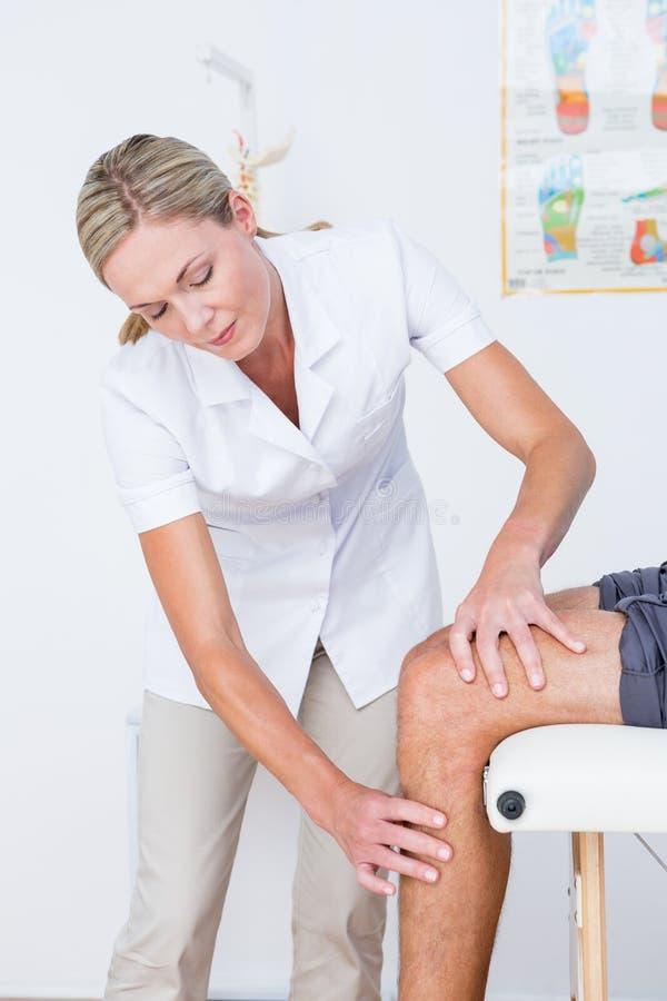 Docteur examinant son genou patient images libres de droits