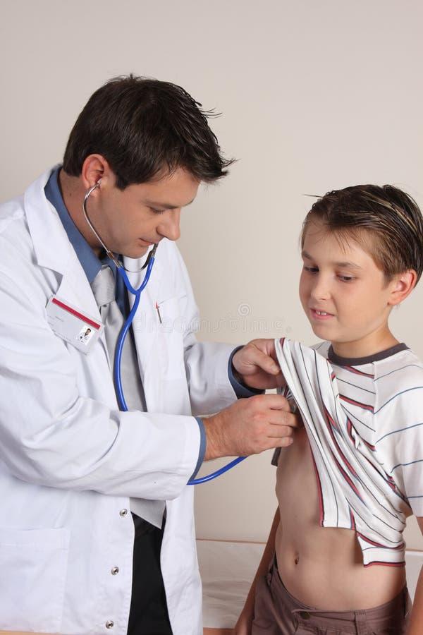 Docteur examinant un enfant image stock