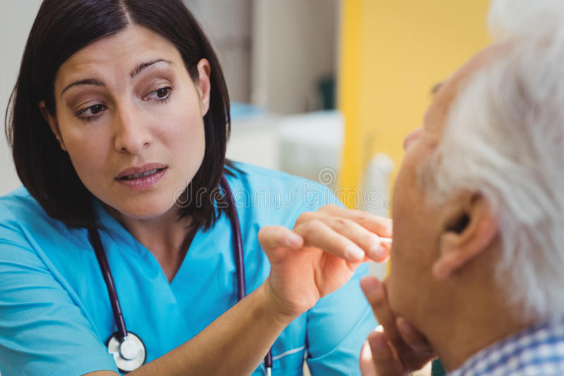Docteur examinant un patient image stock