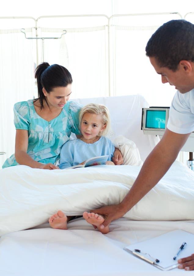 Docteur examinant une fille avec sa mère dans le remorquage images libres de droits