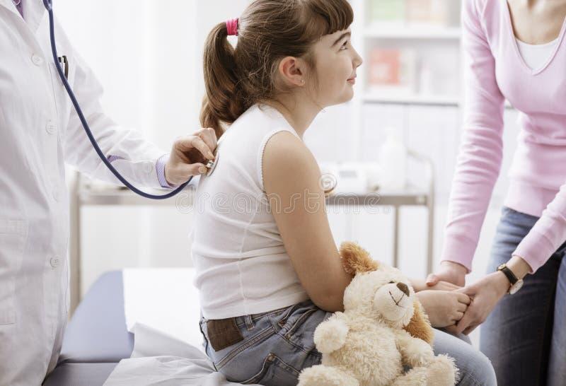 Docteur examinant une fille de sourire mignonne avec un stéthoscope photos libres de droits