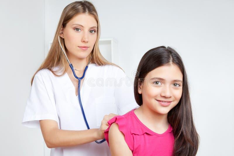 Docteur Examining Child dans la clinique image stock
