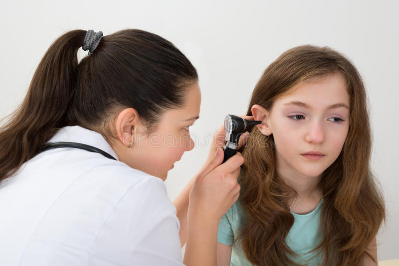 Docteur Examining Patient Ear avec l'otoscope image stock