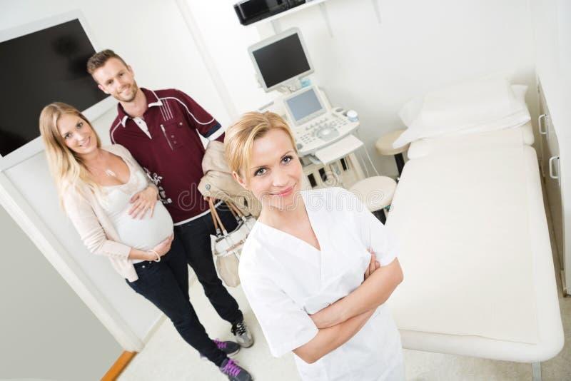 Docteur And Expectant Couple dans la chambre d'examen photographie stock